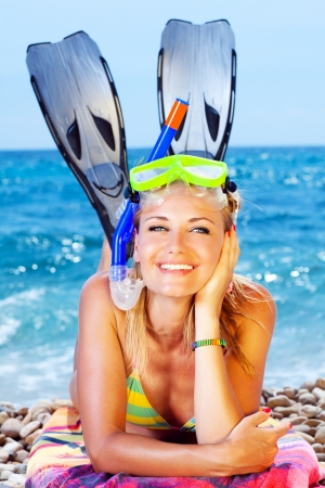 resting mask: Beautiful woman having outdoor fun, female on the beach, happy teen girl wearing mask and fins, water sport, healthy young lady tanning and sunbathing, summer vacation, holidays travel Stock Photo