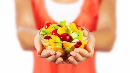 Gesunde Mischung Obstsalat, Nahaufnahme auf frischen Sommer Dessert, hält Frau Mittag Schüssel, selektiven Fokus auf weibliche Hände, essen Mädchen shallow dof, Körpergewicht Pflege, Gesundheit und Ernährung Konzept