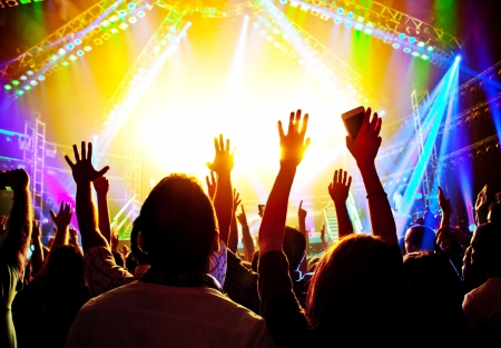 Rock concert, happy people silhouettes, raise up hands, disco party with large group of dancing man, bright colorful stage lights, active lifestyle, music entertainment, nightclub, night life concept photo