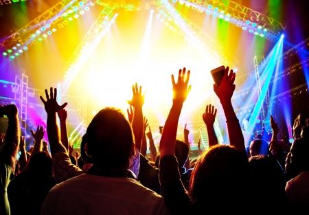 Un concierto de rock, siluetas de la gente feliz, levanta las manos, fiesta disco con el grupo grande de hombres bailando, brillantes luces del escenario de colores, estilo de vida activo, espectáculos de música, club nocturno, el concepto de la vida nocturna