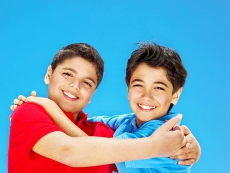 preteen boy: Gar�ons mignons souriant sur le ciel bleu, les pr�adolescents jouer en plein air, les enfants se tenant la main, le meilleur �treinte amis, de beaux enfants en s'amusant, fr�res heureux, la joie de la famille et le concept de bonheur Banque d'images