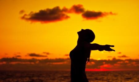 Vrouw silhouet over zonsondergang hemel, donkere zwarte schaduw van vrouwelijk lichaam met de handen omhoog, tienermeisje met plezier buiten, genieten van zonsondergang op het strand, de vrijheid lifestyle, geluk begrip Stockfoto