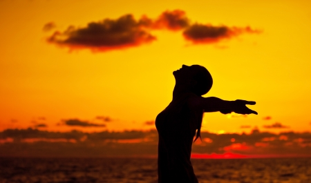Woman silhouette over sunset sky, dark black shadow of female body with hands up, teenage girl having fun outdoor, enjoying sundown on the beach, freedom lifestyle, happiness concept  photo