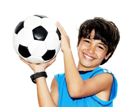 Cute boy playing football, happy child, young male teen goalkeeper enjoying sport game, holding ball, isolated portrait of a preteen smiling and having fun, kids activities, little footballer photo