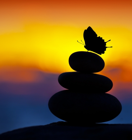 Spa stones balance, colorful summer sky background, silhouette of stacked pebbles and butterfly, beautiful nature, peaceful beach sunset, conceptual image of stable life and harmony Stock Photo