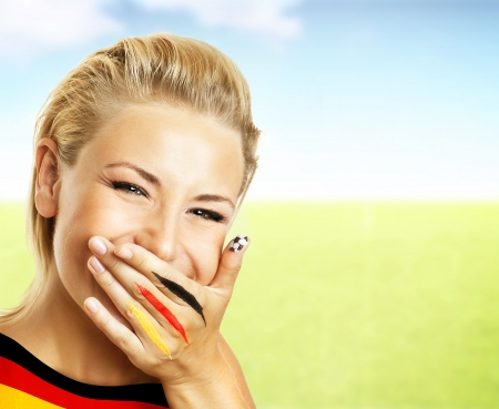 mouth closed: Smiling football fan, closeup on face, female covering mouth with painted in flag colors hand, woman expressing emotions of joy, German team supporter, girl watching game, outdoor field stadium