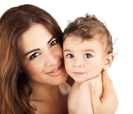 bebes lindos: Lindo bebé sonriendo con la madre, primer plano en los rostros de la familia feliz, la mamá y el niño que tiene cubierta la diversión, los padres la celebración de niño en las manos, niño sano y el retrato de mamá aisladas sobre fondo blanco Foto de archivo
