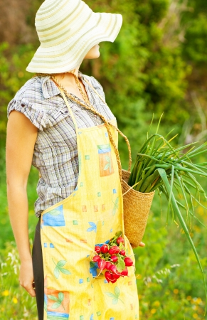 Happy woman gardener working on field, young female holding basket, girl growing organic green vegetables and fruits, summer garden, rural leisure outdoor, lady farmer, radish and onion harvest season photo