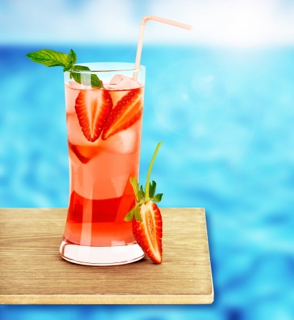 Strawberry juice on the poolside, fresh red berry tropical cocktail on wooden tray, cafe outdoor, beach restaurant, icy cold drink, healthy beverage, vacation and diet concept, food style and design photo