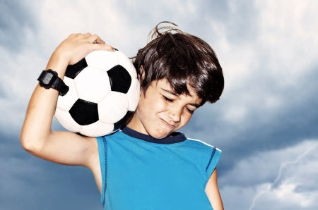 teens playing: Football player celebrate victory, cute boy playing on stadium, kid enjoying team game outdoor, teen holding catching ball, happy child facial expression, sport fan portrait over cloudy sky background Stock Photo