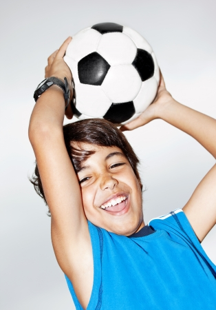 teens playing: Happy jumping boy, cute kid playing football, active child, young male teen goalkeeper enjoying sport game, catching ball, isolated closeup portrait, preteen smiling and having fun, little footballer
