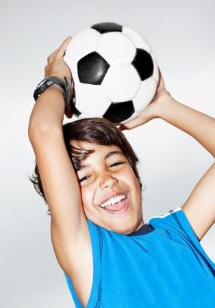 jugando al futbol: Ni�o saltando feliz, el f�tbol chico lindo jugar, ni�o activo, el portero joven adolescente masculino disfrutando de juego del deporte, la bola de captura, closeup retrato aislado, preadolescente sonriendo y divirti�ndose, el futbolista poco
