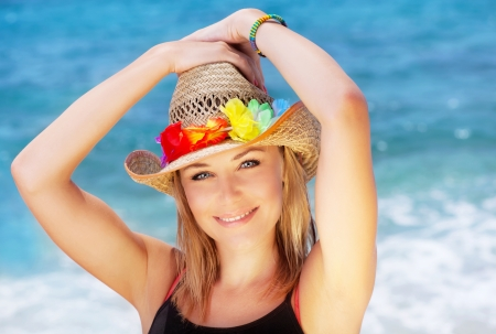 Beautiful female outdoor portrait over blue beach water, happy smiling face, summer fun concept photo