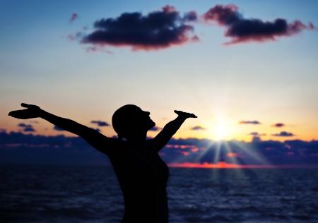 manos levantadas: Silueta de la mujer en cielo del atardecer, la sombra de color negro oscuro del cuerpo de la mujer con las manos arriba, adolescente divirtiéndose al aire libre, disfrutando de la puesta del sol en la playa, estilo de vida de la libertad, el concepto de la felicidad Foto de archivo