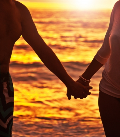 siluetas de enamorados: Feliz pareja caminando por la playa, tomados de las manos, primer plano en la silueta, la mujer y el cuerpo del hombre sobre fondo puesta del sol, viaje rom�ntica luna de miel, vacaciones en familia disfrutando de la vida y la naturaleza, el concepto de amor Foto de archivo