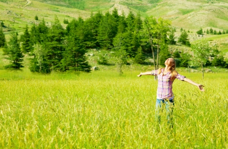 arms raised girl: Happy girl enjoying nature, young woman on wheat field, beautiful female having fun with hands up, freedom concept, summer outdoor vacation, model teen over green natural background, sunny day joy Stock Photo