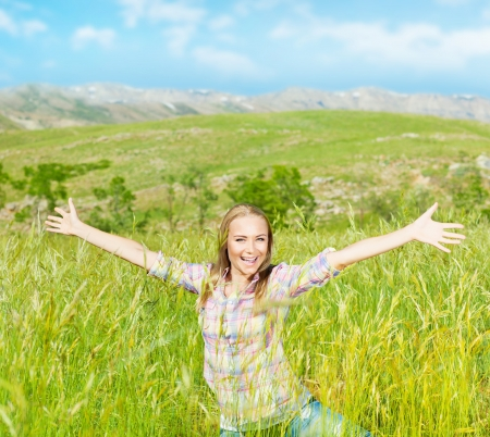 Happy cute girl on wheat field, smiling young lady enjoy open air, beautiful woman raised up hands, pretty teen playing outdoors, attractive female having fun outside, active life and freedom concept photo