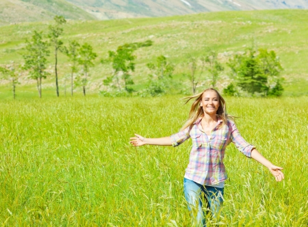 Young happy woman walking on wheat field, cute teen runs on green grass field, carefree girl enjoying peaceful countryside nature, beautiful smiling female have recreation in park, freedom concept photo