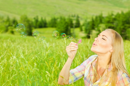Cute girl blowing bubbles outdoors, beautiful woman spending summer holiday in park, happy female enjoying spring vacation, young lady playing on wheat field, pretty teenager relaxed outside photo