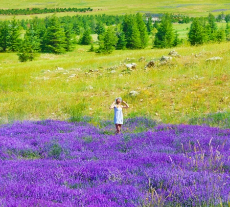 Beautiful girl enjoying lavender field, pretty woman in white dress relaxed on flowers meadow, happy cute female standing on natural floral glade, bright sunny day, vacation and summer holiday concept photo