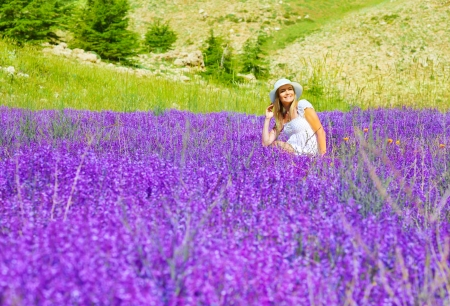 spring hat: Beautiful woman on lavender meadow, pretty smiling girl sitting on floral field, cute happy female enjoying purple flowers, cheerful teenager relaxed outdoors, natural beauty, summer holiday concept Stock Photo