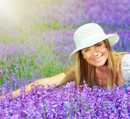 Pretty woman lying down on lavender field at sunny day, beautiful female sitting on purple flowers meadow, cheerful smiling girl enjoying violet floral glade and sun light, portrait of young lady  photo