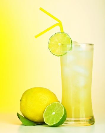 Fresh lemon juice, tasty cold lime drink, healthy fruits and icy beverage, sweet refreshing lemonade, tropical citrus cocktail, full glass of alcohol isolated on yellow background, food still life photo