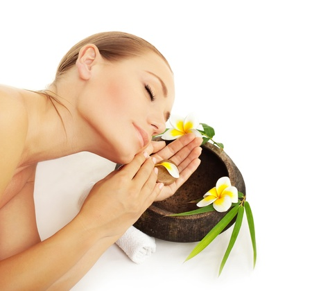 Woman sleeping in spa, beautiful female model enjoying beauty salon, aroma therapy, healthy soft skin, girl face and frangipani flowers, relaxation and wellness concept, isolated on white background photo