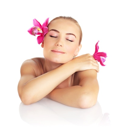 woman lying down: Beautiful sleeping woman in spa salon, pretty female face with pink orchid flower, cute girl isolated on white background, young lady relaxing on massage table, beauty treatment and health care