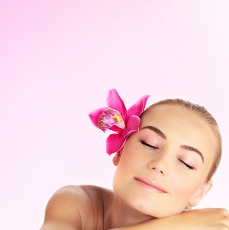 dayspa: Young woman at spa salon, beautiful girl sleeping on massage table, pretty female with pink orchid in her hair, attractive lady relaxed, beauty and health care concept, close up portrait of cute model