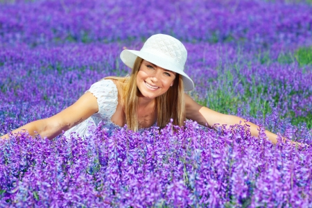 spring hat: Pretty woman lying down on lavender field