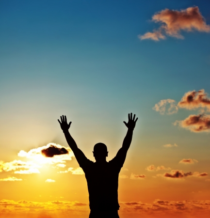 victory: Men silhouette at sunset, human body over natural colorful sky background Stock Photo