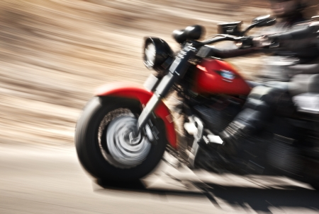 Abstract slow motion, biker riding motorbike, driver racing on the big red bike, side view, blur movement, summer road trip, speed concept photo
