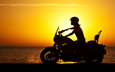 Woman biker over sunset, female riding motorcycle, motorbike driver traveling, girl racing on the beach road, freedom lifestyle  photo
