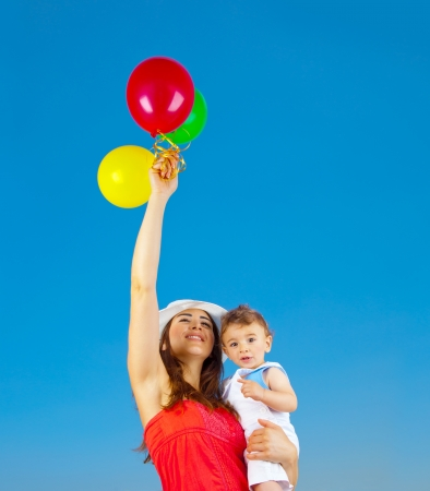 Happy family holding colorful air balloons over blue sky background photo