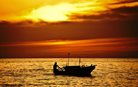Fisherman on the boat over dramatic sunset, male on vessel, beautiful seascape with dark clouds, ship silhouette in ocean over evening sunlight, traveling, holiday, vacation and hobby conception photo