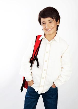 ni�o parado: Bonito ni�o sonriente de la escuela aisladas sobre fondo blanco, bastante masculina adolescente con mochila roja, retrato de la hermosa estudiante morena, ni�o inteligente en concepto de estudio, el conocimiento y la educaci�n