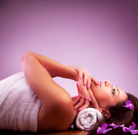 resting: Beautiful girl in spa salon, pretty woman relaxing on massage table, attractive young female isolated on pink background, healthy lifestyle, beauty care, treatment and therapy concept Stock Photo