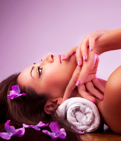 Beautiful relaxing female in spa salon, cute brunette girl with purple flowers in hair isolated on pink background, nice young lady enjoying dayspa, beauty care and healthy lifestyle concept Stock Photo - 14686546