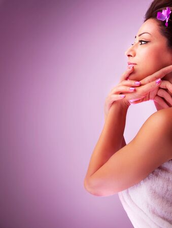 dayspa: Pretty woman in spa salon, beautiful female with violet flower in dark hair isolated on pink background, side view of cute girl face, nice young lady enjoying dayspa, zen balance, beauty care concept  Stock Photo