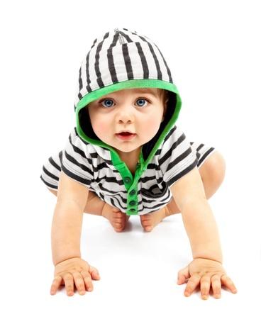 bebe gateando: Lovely boy aisladas sobre fondo blanco, dulce bebé usando deslizadores poco rayados, niño pequeño y encantador en hoodie blanco y negro con interiores Biggin arrastrándose, concepción infancia feliz
