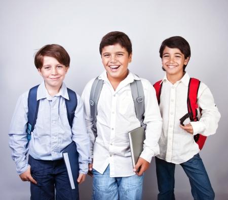 ni�o modelo: Tres colegiales feliz aislado sobre fondo gris Foto de archivo