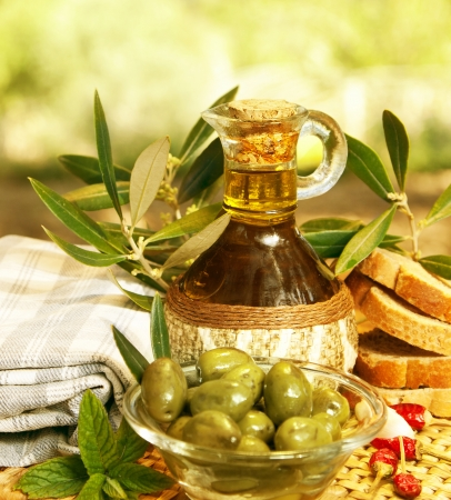 Olive oil in bottle and fresh green olives in glass plate on the table