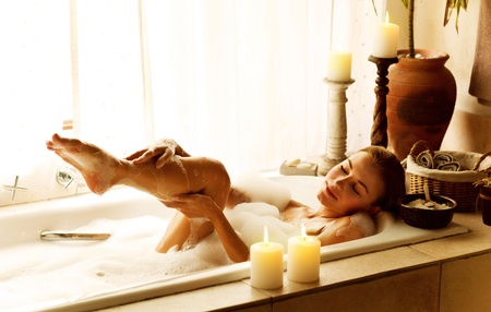 Photo of a woman relaxed at luxury spa salon, picture of young beautiful lady taking bath at home, image of pretty female bathing with soap foam and candles in hotel room, cute girl relax in jacuzzi photo
