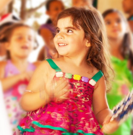 carnival festival: Happy smiling baby girl, adorable cheerful female child enjoying dance on carnival festival, sweet kid having fun on birthday party outdoor, pretty little girl portrait, happiness concept