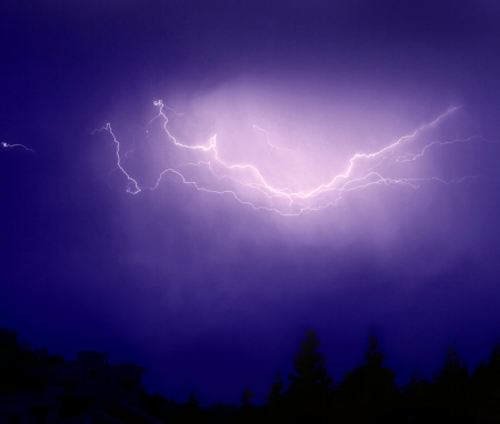 electric spark: Photo of bright lightning over dark blue sky, image of zipper flash above forest, picture of dangerous thunderstorm, abstract background, autumn weather  Stock Photo