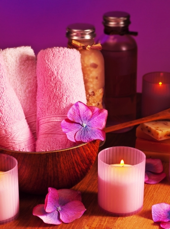 Photo of bath accessories on wooden table over purple background, picture of spa candles, image of alternative treatment items, day spa concept, pink still life, health and beauty care photo