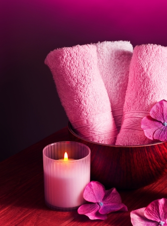 spa still life: Photo of pink spa background, picture of zen candle light, image of fresh soft towel on wooden table, bath accessories, aromatherapy, health and beauty care, luxury spa resort, harmony concept