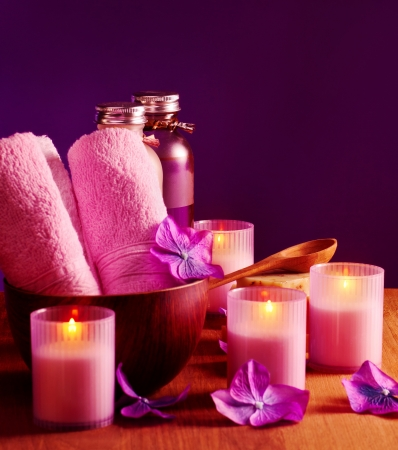 aroma bowl: Photo of spa still life on purple background, picture of pink bath candles and bottles with massage oil, image of soft towel in wooden bowl, aromatherapy, beauty treatment, luxury spa resort