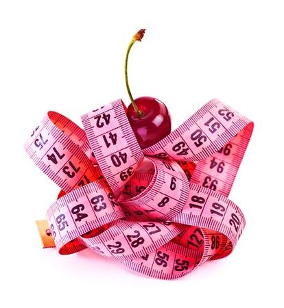 cintas metricas: Cinta métrica con la cereza aisladas sobre fondo blanco, el concepto dieta, comer sano, centímetro a medida rosa, cuidado del cuerpo, el control de exceso de peso, forma delgada